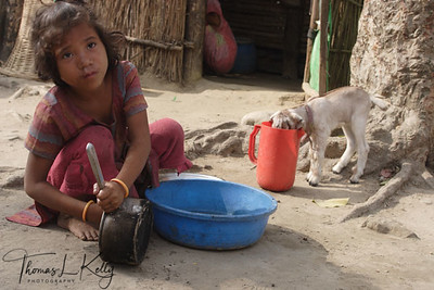 In lots of villages of Nepal; to survive all the members have to contribute labour to make living. This girl is delegated to clean dishes for local tea stalls to supplement family income. Hetauda, Nepal.