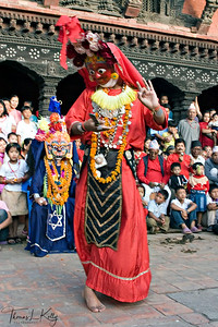 To celebrate Goddess Durga's triumph over the buffalo demon Mahisasur, Asta Matrika dancers perform in Patan's Mul Chowk. men and boys dressed to epresent the mother-earth goddesses energy and act out each gods characteristics.  The performances were initiated in seventeenth century by the Malla king Srinavasa, whose fater built the Krishna temple in Patan. Indrani dances in an orange mask covered with eyes; nobody can hide from the goddess. Maheswari dances in white mask, which represents the female aspect of Shiva, who continually combats demons. Brahmayani, in a yellow mask, represents the human aspect of Brahma, the creator. Kathmandu, Nepal.