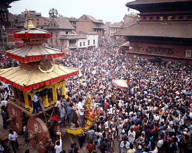 "Bisket Jatra (Bisket festival) is a celebration of victory over the snake gods that ruled the valley in the time of prehistory. It is believed that most of the nagas, or snake gods, evacuated the Kathmandu Valley with the prehistoric draining of its great lake, but a few remained, great serpent kings dwelling in the rivers and the ponds, wielding that most significant of powers, control over rainfall.  On Bisket, ""snake slaughter,"" all the spirits of the gods descend on Bhaktapur, where an eighty-foot lingam (pole) carved from a tree stands fluttering with banners. The banners represent two serpent demons slaughtered by a prince of Malla Dynasty, when they emerged from the nostrils of his sleeping princess.  Crowds follow a procession of two heavy chariots, one carrying Bhairav, the wrathful form of Shiva; the other Bhadrakali, the bloodthirsty form of Goddess Parvati (Lord Shiva's consort). The crowd divides into teams for a tug of war between the chariots. The winners will have good luck in the coming year. Finally, more straining teams compete to bring the giant lingam to earth. The moment it crashes, the old year dies, and so do the snake demons. The Nepalese New Year begins."