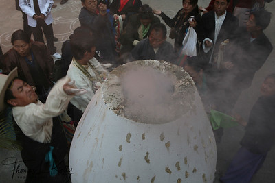 Sherpa devotees toss in juniper offering to the incense burner during Lhosar, The Tibetan New Year. Kathmandu, Nepal.