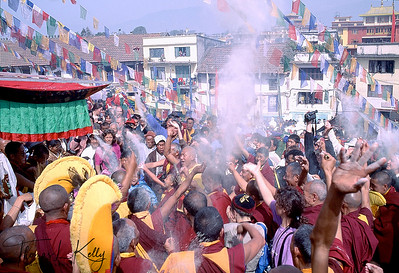 Tibetan Pilgrims throwing Tsaampa (flour) in air during Losar, The Tibetan New Year. Boudhanath Stupa, Kathmandu, Nepal.