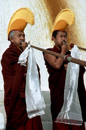 Monks from Gelugpa Sect. blow long horn at the base of Boudhnath Stupa on the occasion of Tibetan New Year, Lhosar. Kathmandu, Nepal.