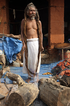A content looking sadhu showcases his dreaded hair, called jata, which are normally worn in a bun on the top of the head save for special occasions. Pashupatinath temple, Kathmandu, Nepal.