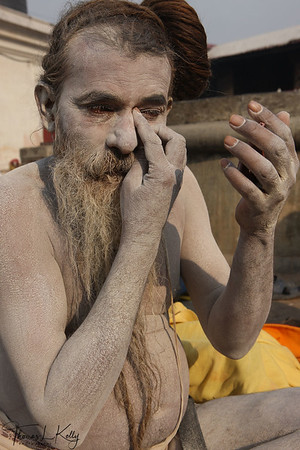 A sadhu's body is a display of his ascetic identity: his clothes or nudity separate him from the populace, covered in sacred ashes while his painted markings, called tilaka, indicate his divine focus of devotion.  Pashupatinath temple, Kathmandu, Nepal.