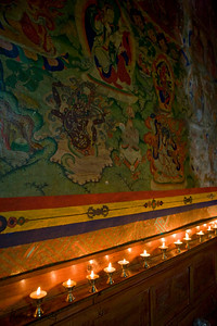 Butter lamps offerings at one of old fresco (Buddhist painting)  inside Chiwong monastery.