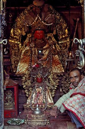 A shrine-keeper sits with  the Dipankar Buddha image Kathmandu, Nepal.