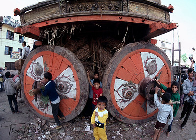 Children play around eye painted wheels of gigantic Rato Machhendranath chariot in Patan. Nepal.