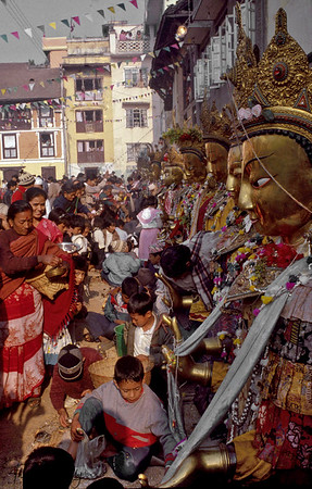 Samyak Festival in Patan, with a line of Dipankara Buddhas receiving offerings of food from Newaro devotees.  Kathmandu, Nepal.