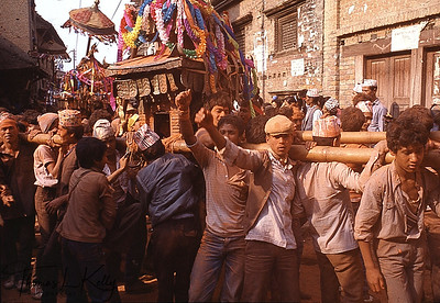 Three miles west of Bhaktapur, at the village of Thimi, the new year is celebrated late into the night with the burning of hundreds of ceremonial oil torches so hot that they drive away the last of winter and bring warm days of sunshine to nourish the crops. On the second day of the new year, neighbourhood deities are carried through the street in temple-like wooden structures called khats. Spectators shower the images and one another with orange powder. To soak one's friends and neighbourhood in dye powder is a token of good wishes and respects, just as it is to honor gods and goddesses.