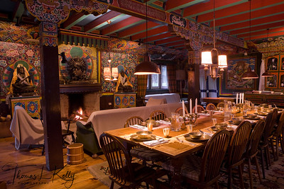 Dining interior of Hotel Del Sherpa. Seen behind is bronze statue of Buddhist deities. Solu, Nepal.
