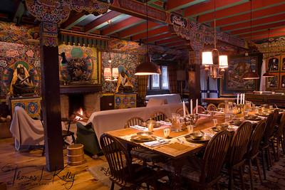 Dining interior of Hotel Del Sherpa. Seen behind is bronze statue of Buddhist deities. Solu, Nepal.