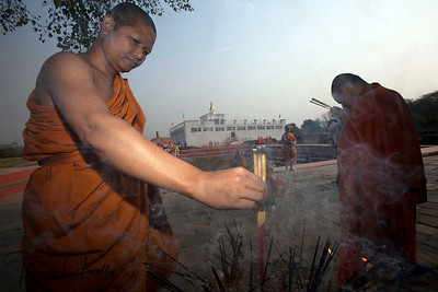 Buddhist pilgrims make incense offering to Mayadevi temple. Lumbini, Nepal.