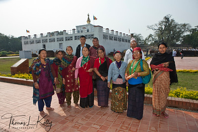 Nepalese Buddhist pilgrims in front of the famous Mayadevi Temple in Lumbini. Inside the temple is a marker stone, said to mark the exact birthplace of Buddha. The pond in front of the temple is said to be the place where Mayadevi bathed before she went into labour. Nepal.