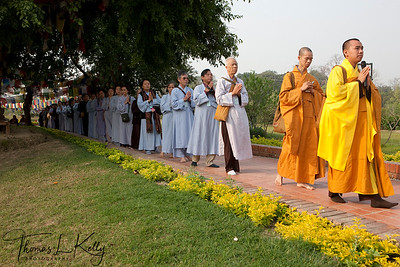 Buddhist pilgrims circumambulate the Mayadevi temple and the pond in front of it. Lumbini, Nepal.