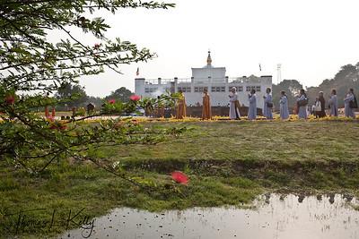 Buddhist pilgrims circumambulate the Mayadevi temple and the pond in front of it. Lumbini, Nepal.