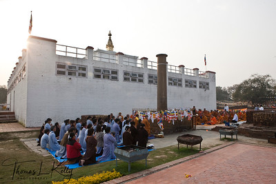 Buddhist pilgrms fold hands for early morning prayer in front of the Mayadevi Temple in Lumbini. The center piece decorated with flags is Ashoka pillar constructed by an Indian Emperor, Ashoka. Nepal.