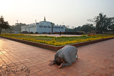 Buddhist monk make prostration as he circumambulates the Mayadevi Temple in Lumbini. Nepal.