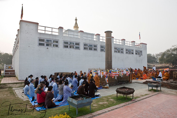 Buddhist pilgrms fold hands for early morning prayer in front of the Mayadevi Temple in Lumbini. Decorated with flags is Ashoka pillar constructed by an Indian Emperor, Ashoka. Nepal.