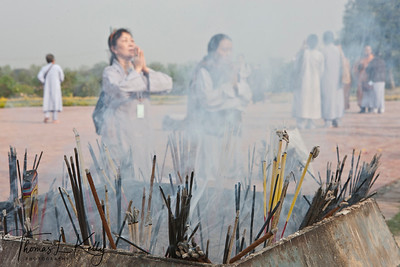 Buddhist pilgrims make incense offering in front of the Mayadevi temple . Lumbini, Nepal.