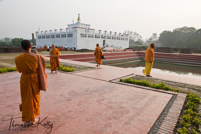Thai monks take photo in front of the Mayadevi Temple in Lumbini. Inside the temple is a marker stone, said to mark the exact birthplace of Buddha. The pond in front of the temple is said to be the place where Mayadevi bathed before she went into labour. Nepal.