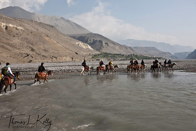 Crossing over rivers on horseback, uncrossable except April-May and make  way through wild, raw and steep terrain reaching a plateau. Mustang, Nepal.