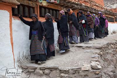 Mustangi women spin prayer wheel at Lo Ghyekar Goempa. Mustang, Nepal.