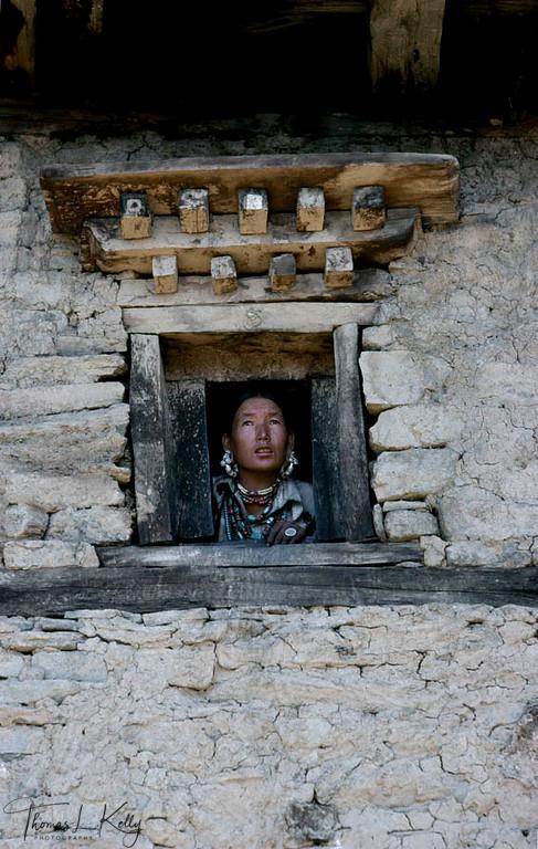 A Bhotia women opeeking out from wooden window.