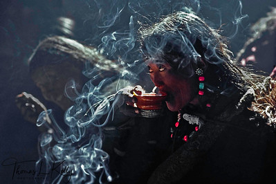 Like an actress caught off –stage, a wedding guest sips Tibetan salt-butter tea from a hand-carved wooden tea cup. Smudges of butter, acting as a blessing, adorn the tea cup. Light from the roof cutout cascades into the smoky dharamsala. Curling incense dances among the shadows of the finely  dressed  guests .