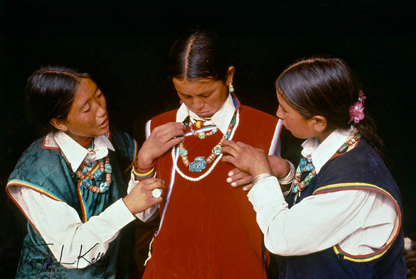 Young sister's of the grooms' play dress-up with elaborate turquoise earrings worn on ceremonial occasions. Humla, Nepal.