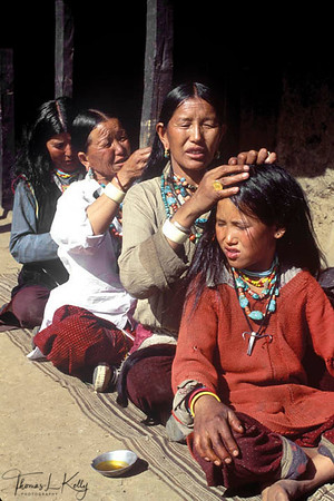 On the wedding day, Mothers' and daughters' sit in a line oiling and braiding each others' hair.