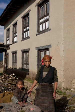 Sherpa mother wearing her traditional attire called tongkok with colourful striped apron tied from waist called pangden. Married Sherpa women tie pangden whereas unmarried Sherpa women just wear tongkok. Solu Khumbu, Nepal.