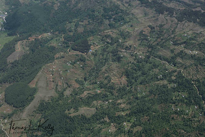 Aerial view of hills and houses, approaching Lukla. Everest region of Nepal.