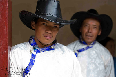 Sherpa men wear cowboy hat and chubas. (Chhuba is a long sleeved robe, which fall to slightly below knee. It is tied with the waist with a cloth sash called kara, creating a pouch like space calle tolung, which can be used for storing and carrying small items. Traditionally, chhuba were made from the thick homespun wool, or a variant called lokpa made from sheepskin. Chhubas are worn over raatuka, a blouse traditionally made out of white raw silk, trousers called kanam, and outer jacket called tetung.  Solu Khumbu, Nepal.