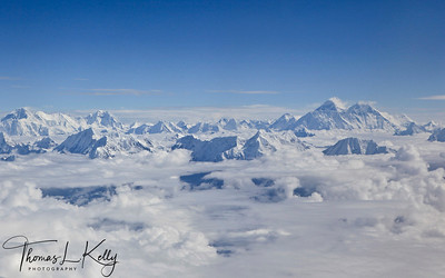 Various Mountains allong with Chomolong Mo/Mt. Everest floating in clouds. Aerial shot on the way to Lhasa from Kathmandu.