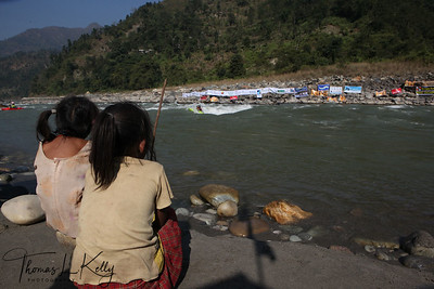 Local girls observe kayakers performing freestyle.  Trisuli, Nepal.