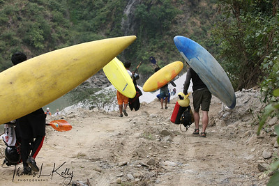 Paddlers carry their kayak to the start point for Downriver challenge. Paddlers race from a Le Mans style mass start, head to head down a stretch of challenging class 4 whitewater. Trisuli, Nepal.