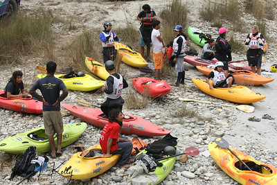 Paddlers carry their kayak to the start point for Downriver challenge.  Trisuli, Nepal.