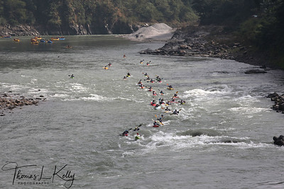 Paddlers race from a Le Mans style mass start, head to head down a stretch of challenging class 4 whitewater. Trisuli, Nepal.