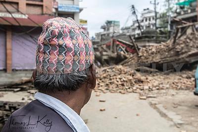 A Newari man looks at a fallen temple in dismay. Patan, Kathmandu