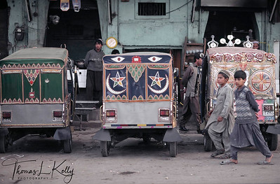 Teenage Afgan boys pass by traditionally decorated auto-rickshwas.  Boys who sleep in the bus terminal complain of overwork and sexual abuse (sometimes by the police) and sometimes mysteriously disappear. One cop said, 'These bastards deserve it. Adda Pir Wadhai Terminal, Rawalpindi.