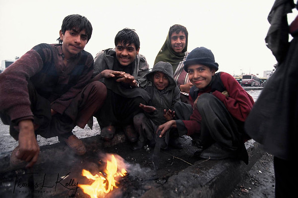 Bus cleaner boys warm themselves by a fire of while waiting fro arriving buses to service. Adda Pir Wadhai Terminal, Rawalpindi.