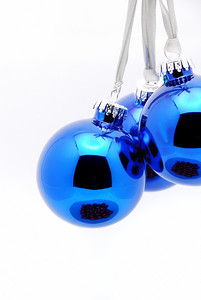 Blue glass christmas tree ornaments over white