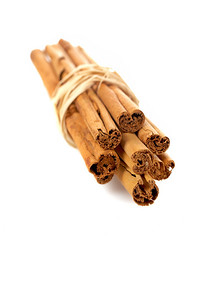 Sticks of cinnamon joined with string on the white background. Shallow DOF and soft shadow