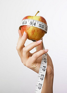 Hand holding an apple with a tape measure wrapped around it. Concept for dieting.