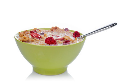 Cornflakes of fruits with the spoon inside the green bowl, reflected on white background. Shallow DOF