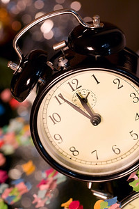Vertical image of clock standing on a table with confetti