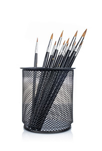 Assortment of various paintbrushes in the basket, reflected on white background