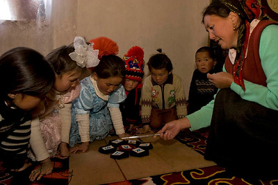 Students use felt-shapes, coloured bone and alphabet cut outs at kindergarten. Satellite Kindergarten (SKG) in Kabylanlal, Kyrgyz Republic.
