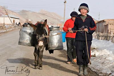 Kyrgyz children enjoy helping their parents in their household work. Children hauling water from river nearby. Kyrgyz Republic.