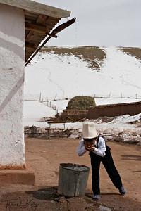 Kyrgyz boy drinks water falling from roof.  Kyrgyz Republic.
